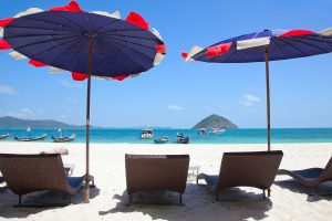Parasols and sunbeds on the beach • Beach Holidays by Holiday Hamster