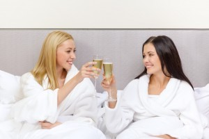 Bride to be and Maid of Honour with champagne glasses in bed • Hen Party by Holiday Hamster