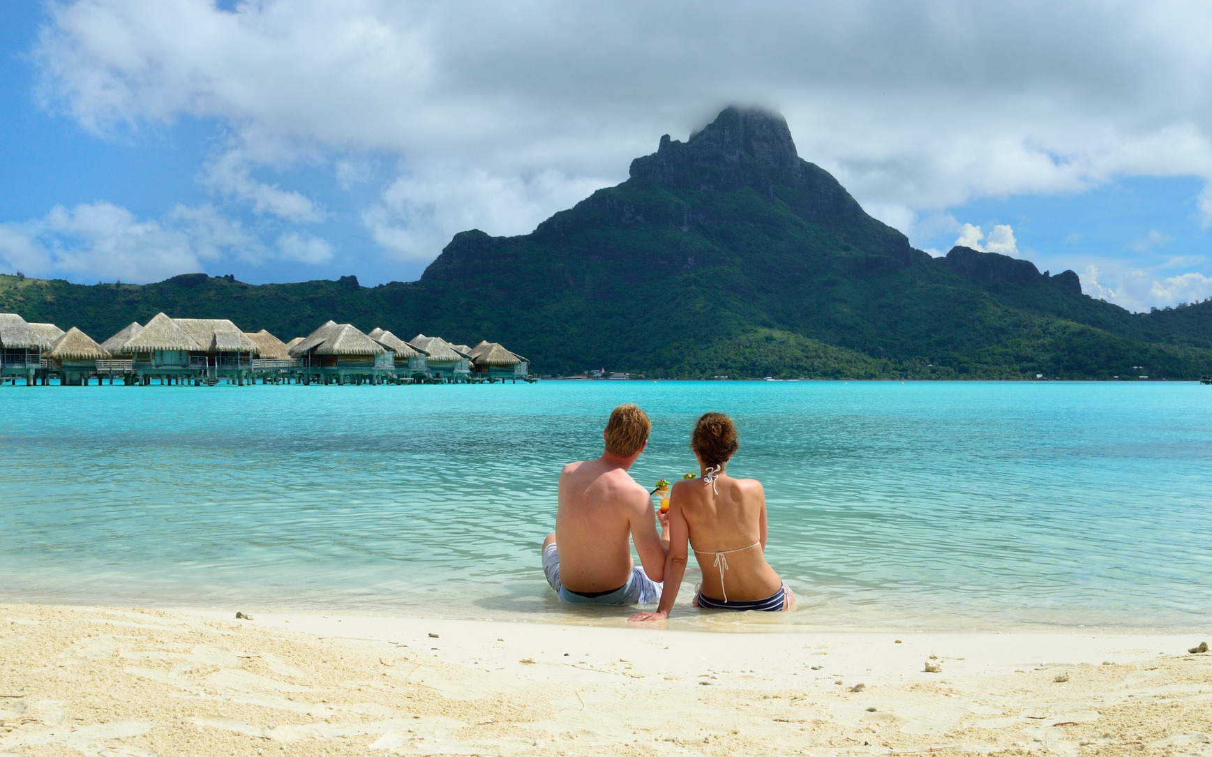 Honeymoon couple on a beach in Bora Bora • Honeymoons by Holiday Hamster