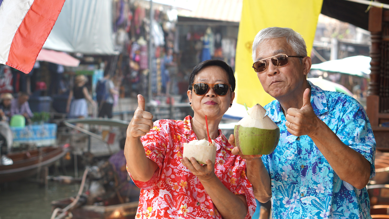 Asian couple drinking coconut juice at a floating market, Thailand