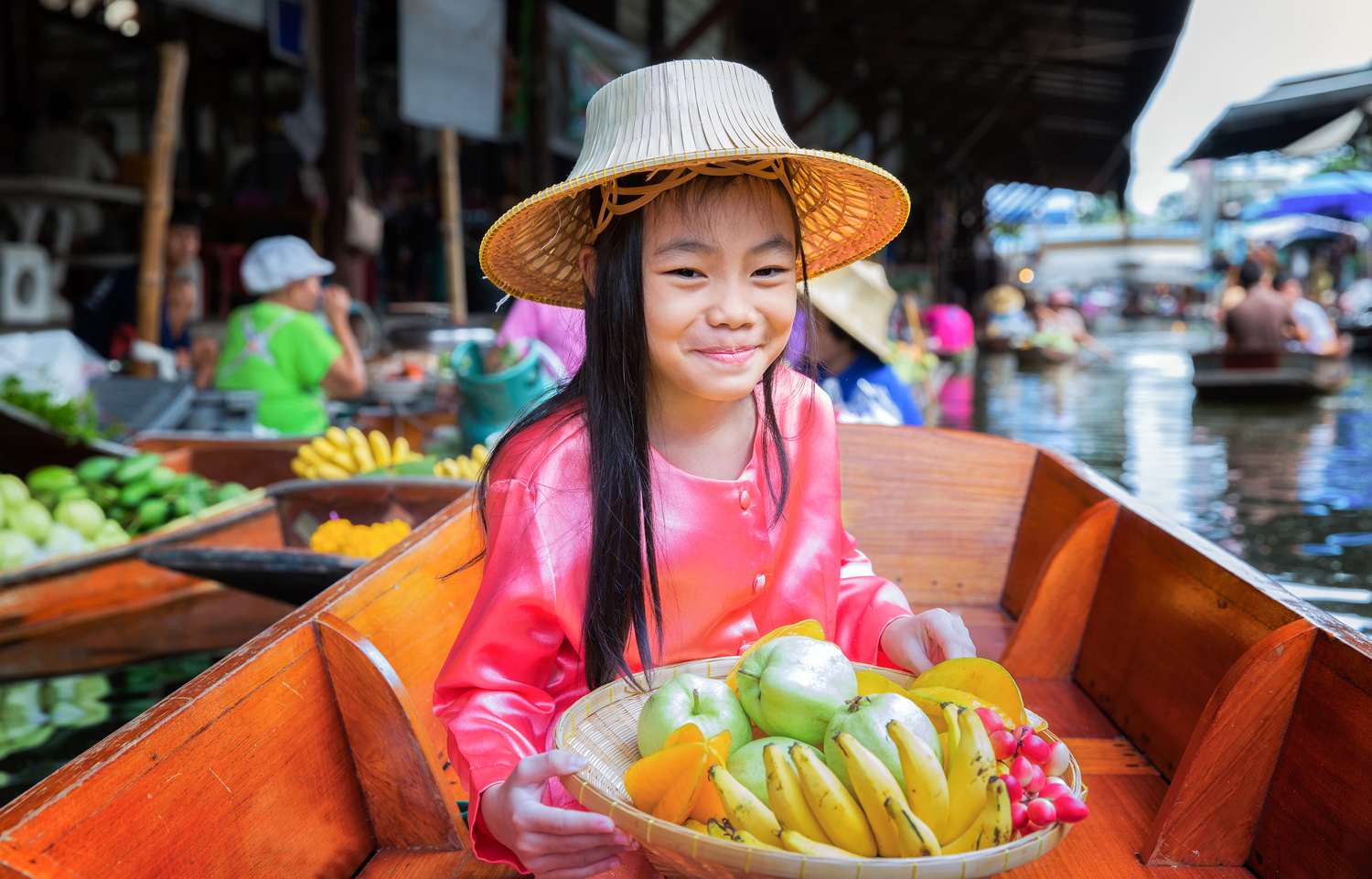 Child sat on a boat, holding a fruit basket in a traditional floating market, Thailand