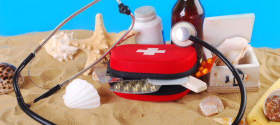 First Aid box with medicines, thermometer and stethoscope on the beach