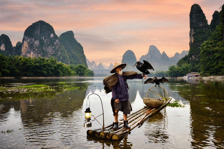 Fisherman on Li River in front of Karst mountains, Guangxi China