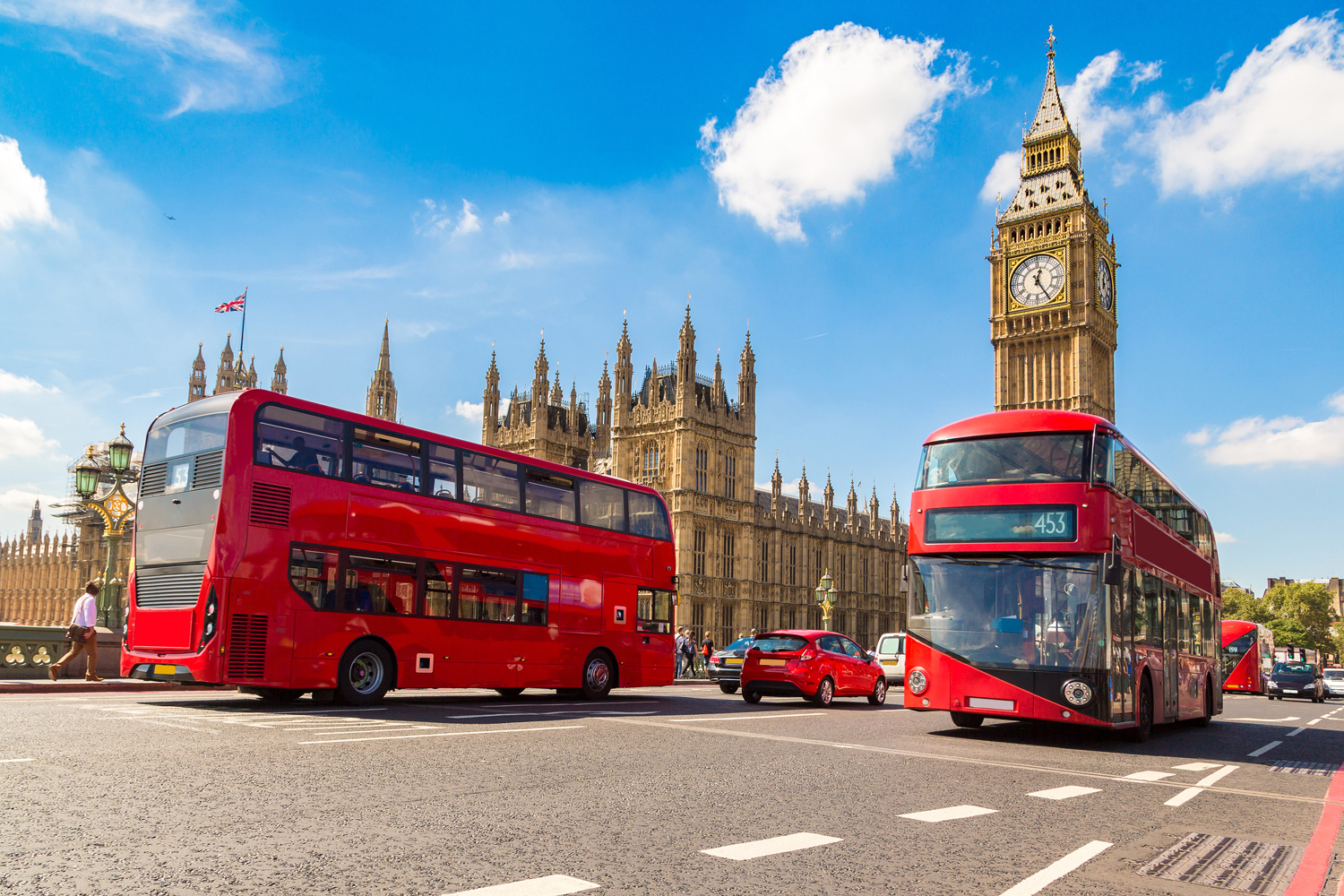 Iconic London red bus driving on Westminster Bridge past Big Ben, in London, England