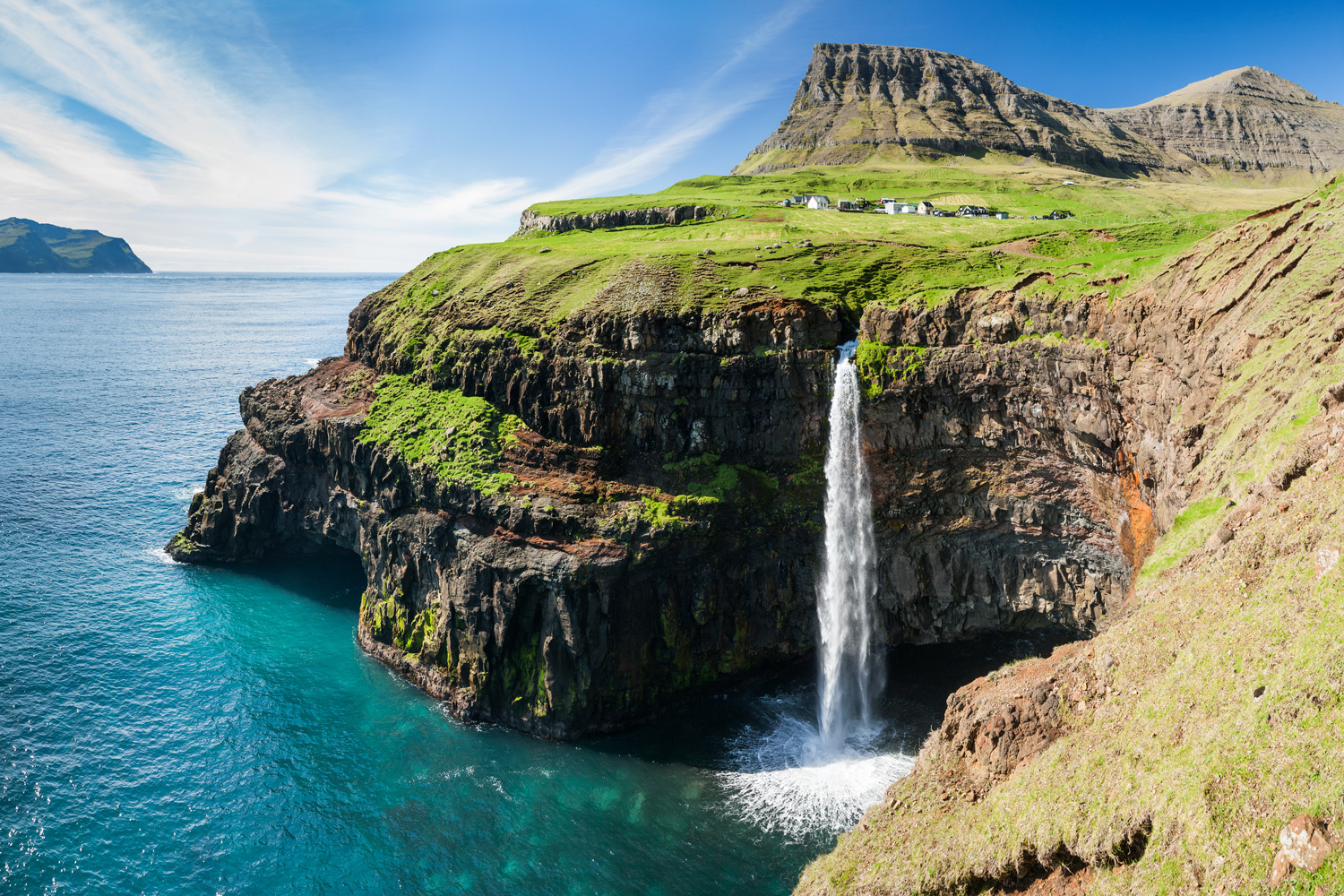 Waterfall on Faroe Islands with Gasadalur village in background